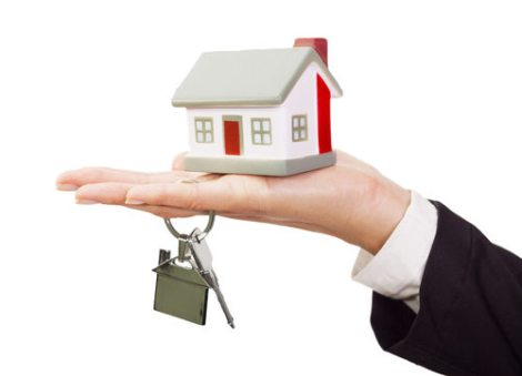 miniature-model-house-and-keys-resting-on-a-female-hand