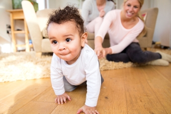 Female couple watch proudly as their baby son crawls along the floor